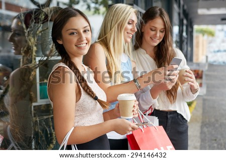 portrait of beautiful teen girl shopping in city with friends standing outdoors with mobile cell phone - stock photo