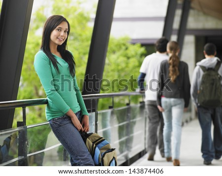 Portrait of beautiful teenage girl leaning against railing in university corridor - stock photo