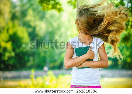 Portrait of beautiful teenage wind with flying hair, against green of summer park. - stock photo