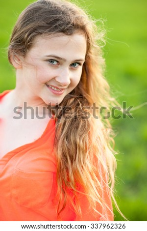 Portrait of beautiful teenager girl  in a bright orange shirt. Wind sways her hairs. Evening back light. Green field on a background. - stock photo