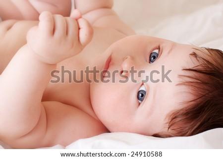 portrait of beautiful thoughtful baby on white bedsheet - stock photo