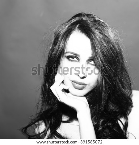 Portrait of beautiful thoughtful young sensual woman with long lush brunette hair and bright makeup looking forward in studio black and white, square picture - stock photo