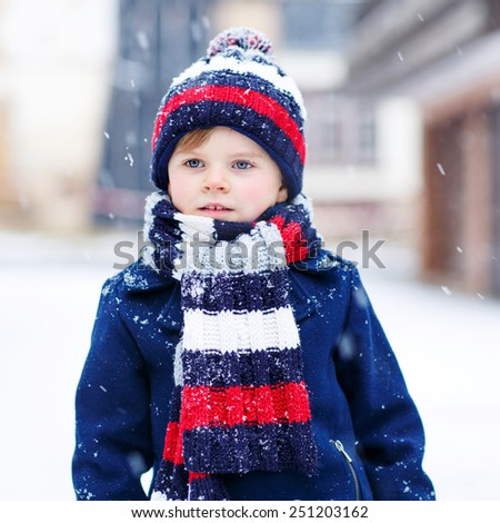 Portrait of beautiful toddler child, boy, in winter clothes with stripes, outdoors, during snowfall on cold day. Active outoors leisure with kids in winter. - stock photo