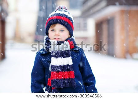 Portrait of beautiful toddler child, boy, in winter clothes with stripes, outdoors, during snowfall on cold day. Active outdoors leisure with kids in winter. - stock photo
