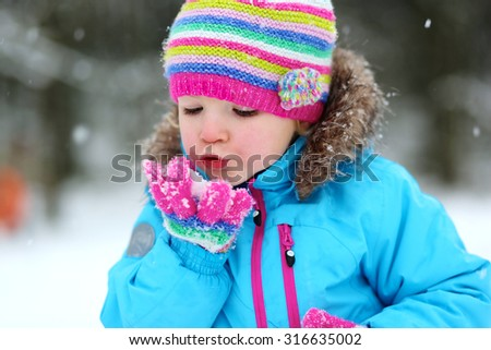 Portrait of beautiful toddler girl playing outdoors with snow. Happy little child wearing colorful knitted hat and blue coat enjoying winter day int he park. - stock photo