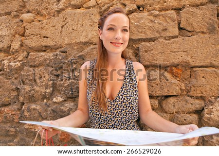 Portrait of beautiful tourist woman visiting destination city against a rough old textured stone wall using a map, sightseeing on a summer holiday. Travel, tourism and shopping on vacation, outdoors. - stock photo