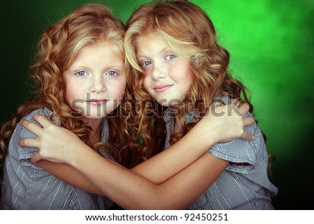 Portrait of beautiful twin sisters holding each other - stock photo