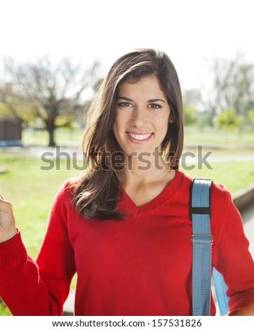 Portrait of beautiful university student smiling on campus - stock photo