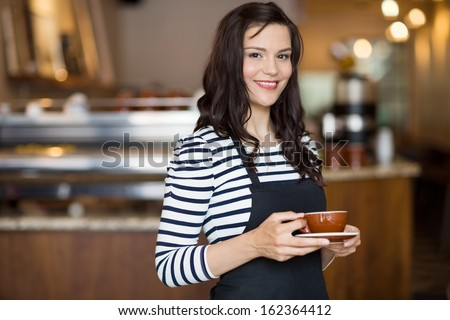 Portrait of beautiful waitress holding coffee cup while standing in cafeteria - stock photo