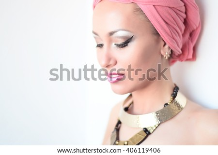 Portrait of beautiful white-skinned girl in a pink turban, african queen style - stock photo