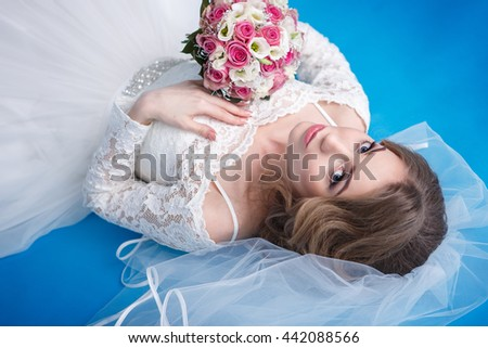 Portrait of beautiful wife's wedding on a blue background - stock photo