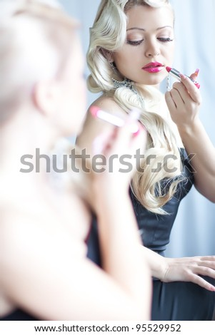 Portrait of beautiful woman applying lipstick