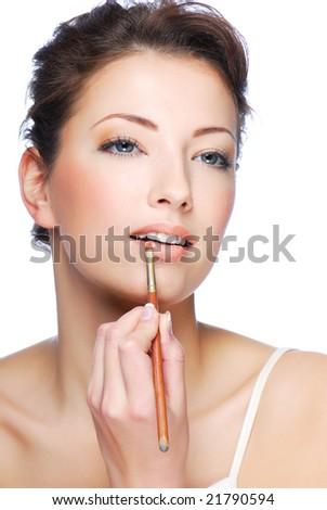 Portrait of beautiful woman applying lipstick using lip concealer brush - stock photo