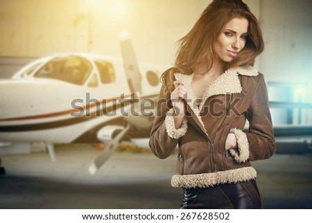 Portrait of beautiful woman aviator in airport  - stock photo