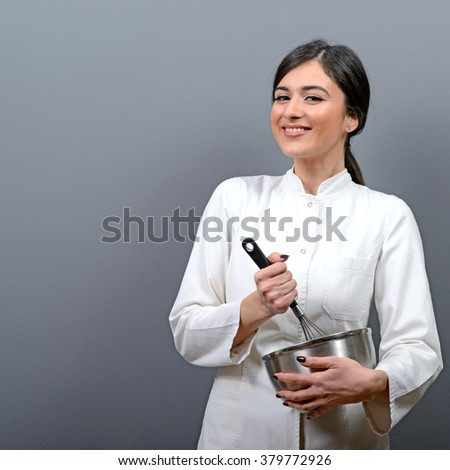 Portrait of beautiful woman chef mixing in a bowl against gray background