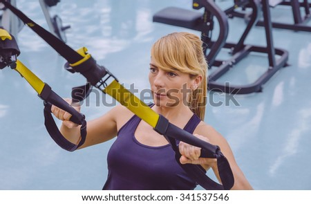 Portrait of beautiful woman doing hard suspension training with fitness straps in a fitness center. Healthy and sporty lifestyle concept. - stock photo