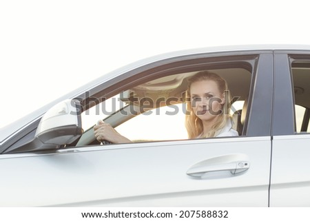 Portrait of beautiful woman driving car - stock photo