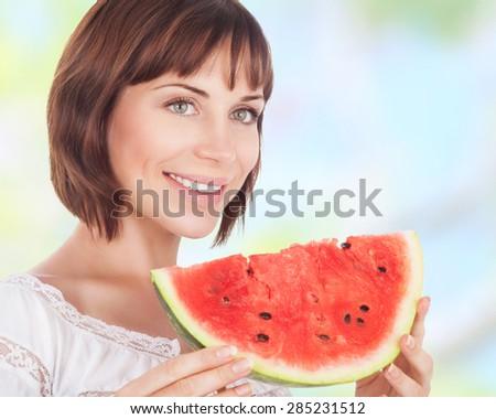 Portrait of beautiful woman eating fresh red ripe watermelon outdoors, tasty dessert of summer season, healthy nutrition - stock photo