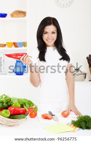 portrait of beautiful woman hold red pepper in the kitchen, looking at camera happy smile - stock photo