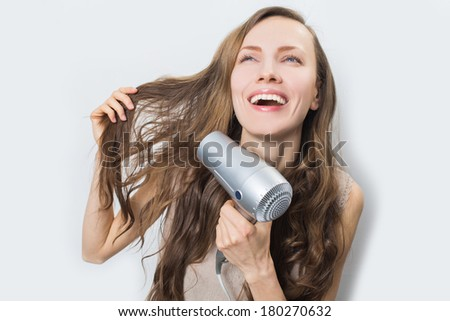 Portrait of beautiful woman holding blow dryer happy smiling