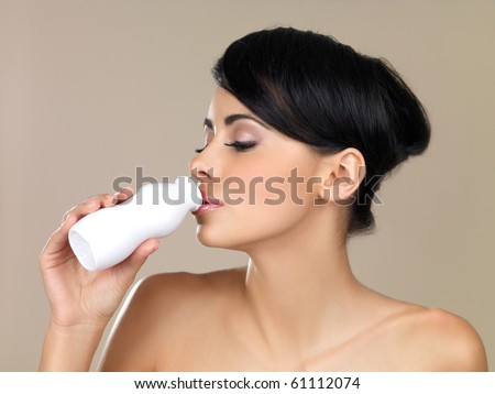 Portrait of beautiful woman, holding bottle of milk - stock photo