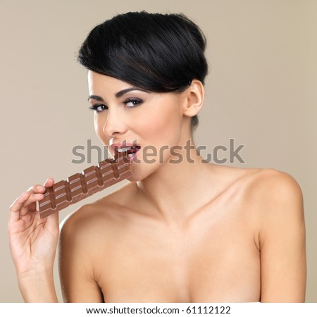 Portrait of beautiful woman, holding chocolate bar - stock photo