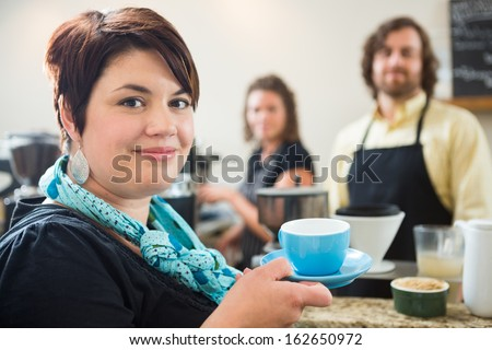 Portrait of beautiful woman holding coffee cup with owners in background in coffee shop - stock photo