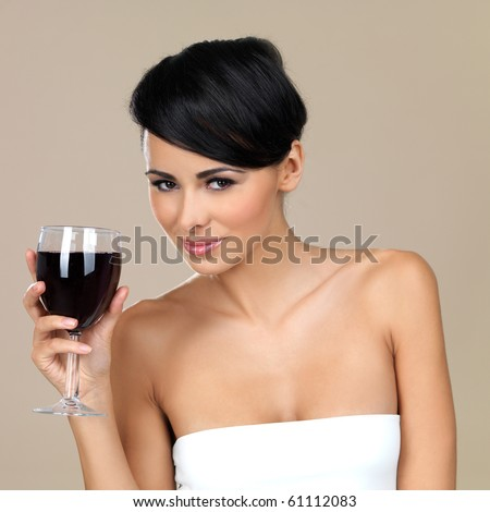 Portrait of beautiful woman, holding glass of red wine - stock photo