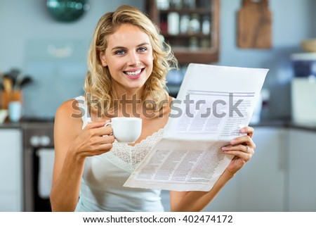 Portrait of beautiful woman holding newspaper and coffee cup at home - stock photo