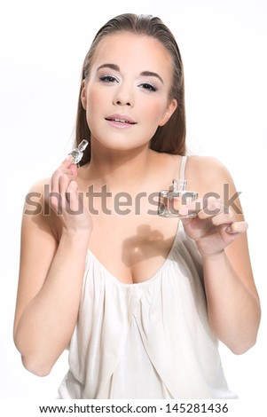 Portrait of beautiful woman holding perfume on white background