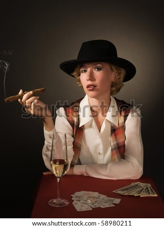 Portrait of beautiful woman in a black hat with a cigar - stock photo