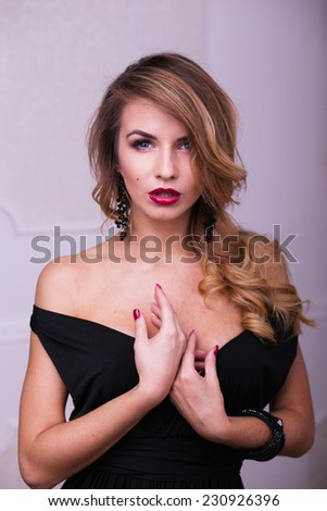 Portrait of beautiful woman in black dress in studio on white wall background - stock photo