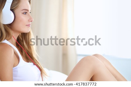 Portrait of beautiful woman in morning listening music sitting on bed at home - stock photo