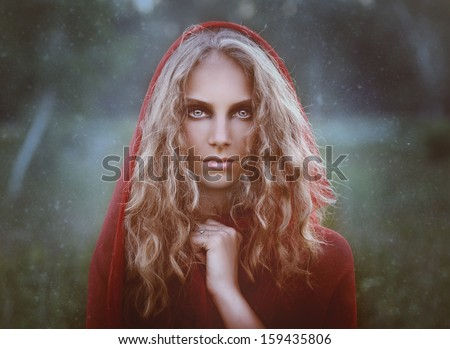 portrait of beautiful woman in red hood - stock photo