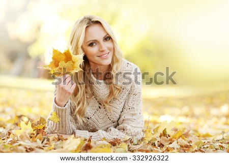 Portrait of beautiful woman laying in autumn park with maple leaves - stock photo