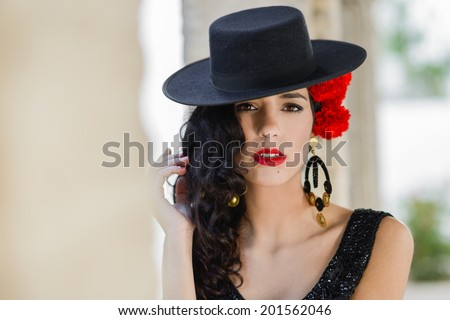Portrait of beautiful woman, model of fashion, wearing spanish hat and red carnations in her hair - stock photo