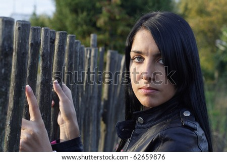 Portrait of beautiful woman near fence. More images of this models you can find in my portfolio - stock photo