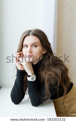 portrait of beautiful woman near window - stock photo