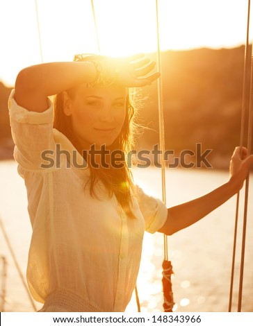 Portrait of beautiful woman on yacht deck in warm yellow sunset light, attractive model posing on sailboat, luxury cruise on the sea, summer vacation concept - stock photo