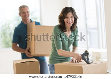 Portrait of beautiful woman packing cardboard box with man standing in background at home