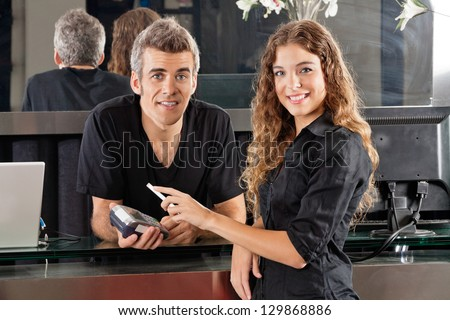 Portrait of beautiful woman paying with mobilephone over electronic reader and hairdresser standing at salon counter