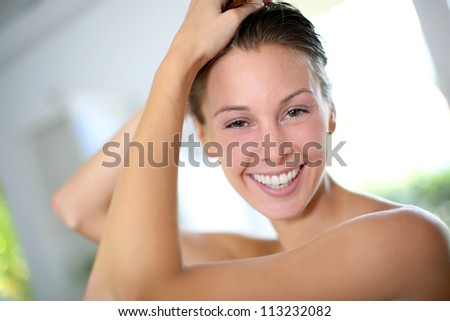 Portrait of beautiful woman putting her hair up