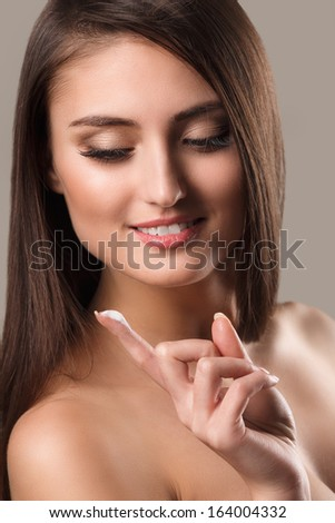 Portrait of beautiful woman, she has cream on her finger