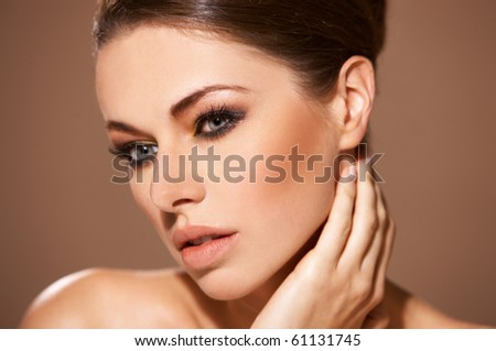 Portrait of beautiful woman she is doing neck massage isolated on beige