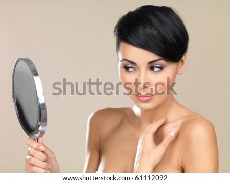 Portrait of beautiful woman, she is looking at the mirror - stock photo