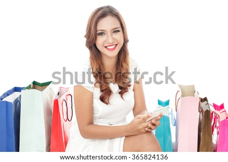 portrait of beautiful woman sitting between shopping bags while holding mobilephone isolated on white background