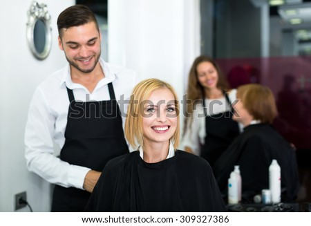 Portrait of beautiful woman sitting in a beauty salon in a black peignoir while hairdresser is preparing to wash her hair - stock photo