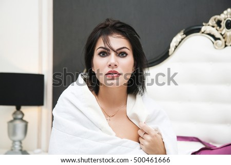 portrait of beautiful woman sitting in bed wrapped in a blanket