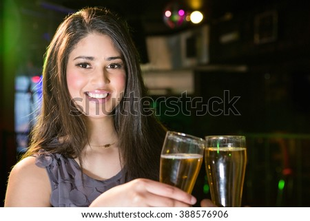 Portrait of beautiful woman smiling while toasting her beer glass in bar