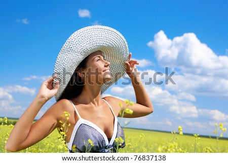Portrait of beautiful woman standing in the middle of meadow and looking upwards with smile - stock photo